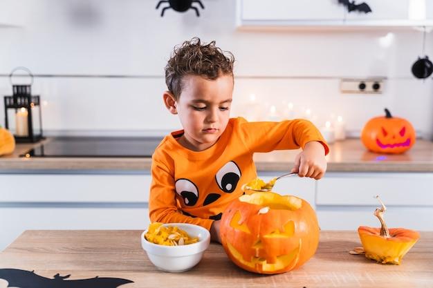 Süßer junge, gekleidet in ein halloween-kürbis-t-shirt, der einen halloween-kürbis leert und ihn für den ...