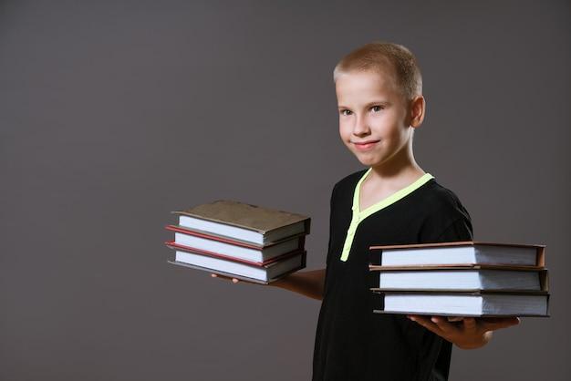 Süßer junge in einem schwarzen t-shirt hält stapel bücher an einer grauen wand