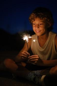 Süßer junge mit glänzendem bengalischem licht