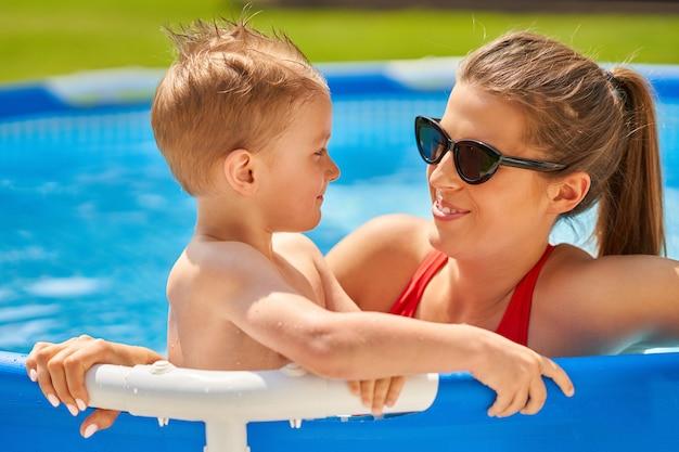 Süßer junge mit seiner mutter, die im sommer in einem wasserbecken spielt