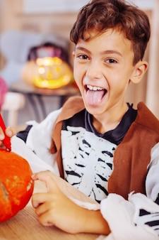 Süßer junge. netter dunkeläugiger junge, der skelettkostüm für halloween-familienhausparty trägt kürbis trägt