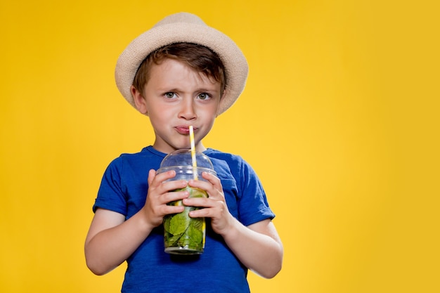 Süßer junge trinkt mojito-cocktail aus plastikbecher