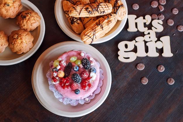 Süßer käsekuchen mit frischen beeren und joghurtcreme und holzschild its a girl. babyparty-party-süßigkeiten.