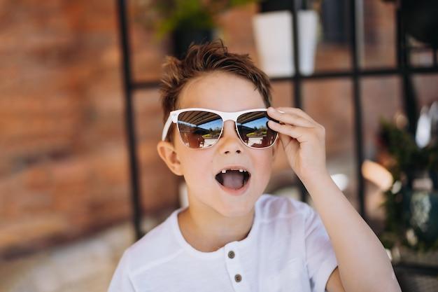 Süßer kauasischer junge in weißem t-shirt und sonnenbrille, der für die kamera posiert und seinen verlorenen zahn zeigt