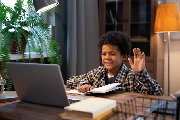 Süßer kleiner afrikanischer schuljunge in freizeitkleidung winkt jemandem mit der hand, während er am tisch vor dem laptop sitzt und im video-chat kommuniziert