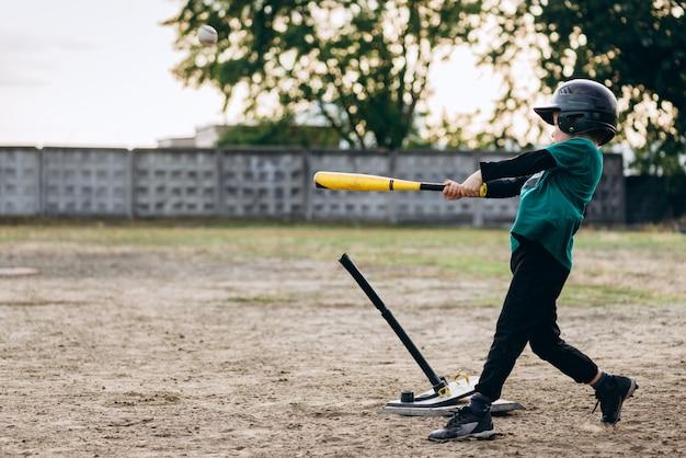 Süßer kleiner baseballspieler schlägt den ball mit einem baseballschläger