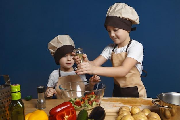 Süßer kleiner junge, der kochmütze trägt, die am küchentisch steht