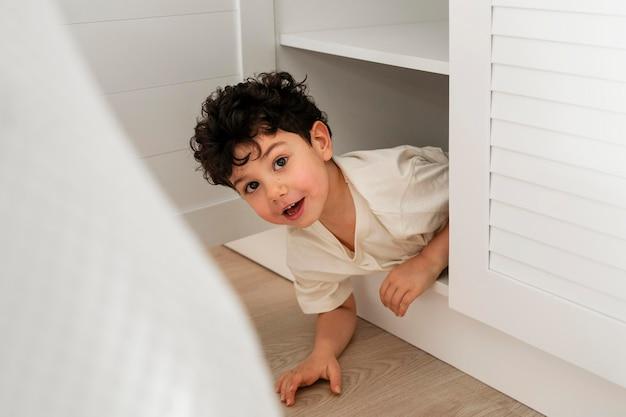 Süßer kleiner junge, der sich im kleiderschrank versteckt