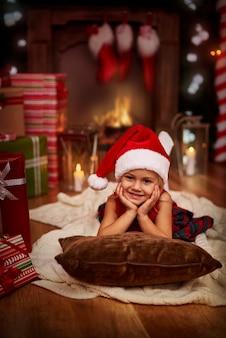 Süßer kleiner weihnachtsmann, der an heiligabend entspannt