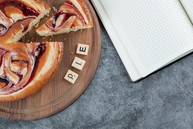 Süßer kuchen auf einer holzplatte mit buchstabenwürfeln herum