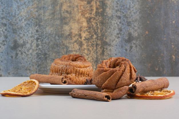 Süßer kuchen mit orangenscheiben und zimt auf weißem teller.