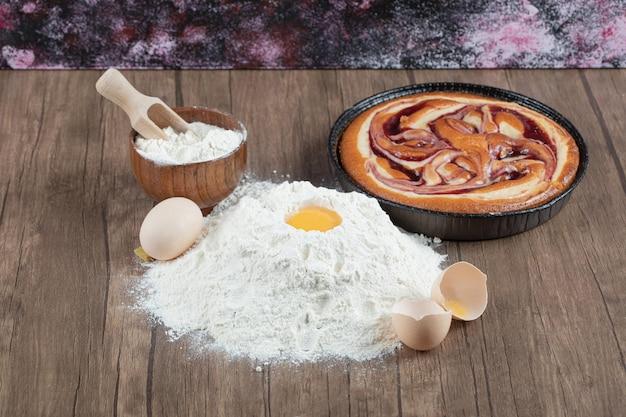 Süßer kuchen mit zutaten auf holztisch.