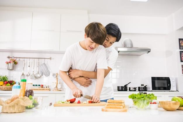 Süßer lgbt junger asiatischer mann umarmt seinen freund, während er apfel hackt, um salat in der küche zu machen. gesunde ernährung für homosexuelle gleichgeschlechtliche familienpaare zu hause.