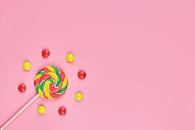 Süßer lutscher und süßigkeit auf rosa hintergrund, kopienraum. liebe zu bunten süßigkeiten im kindheitskonzept