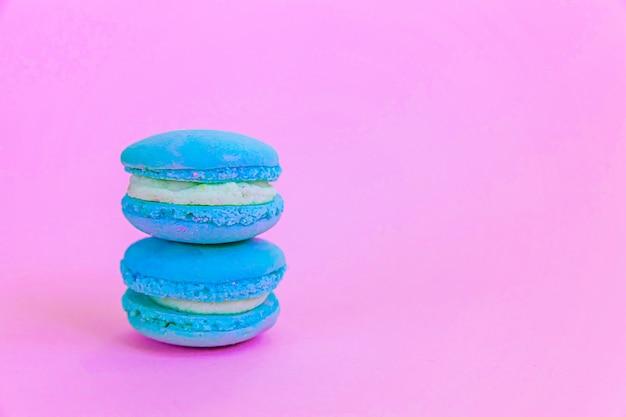 Süßer mandel-buntes einhorn-blau-macaron oder makronen-dessert-kuchen einzeln auf trendigem rosa pastellhintergrund. französischer süßer keks. minimales lebensmittelbäckereikonzept. platz kopieren