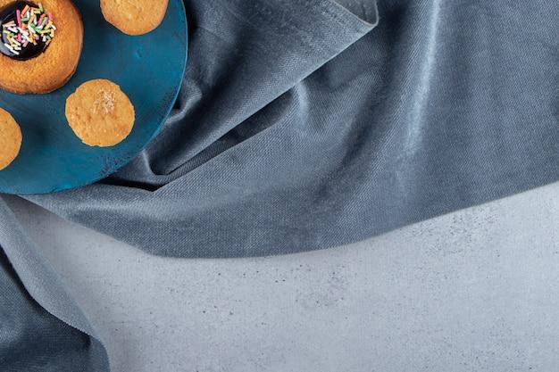 Süßer minikuchen mit gelee und keksen auf blauem brett. foto in hoher qualität