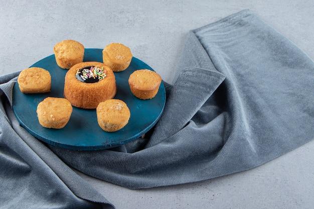 Süßer minikuchen mit gelee und keksen auf blauem brett