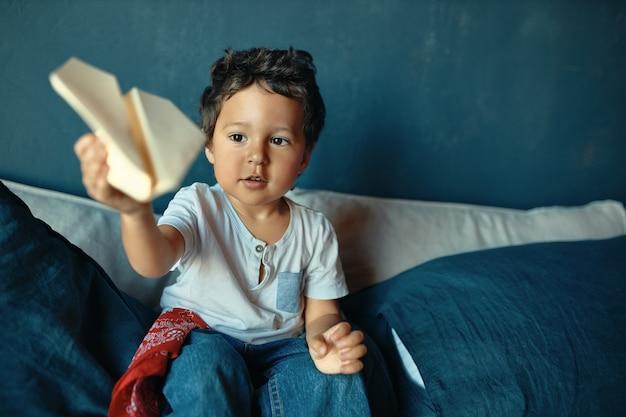 Süßer molliger dunkelhäutiger kleiner junge, der auf bett sitzt, aktive spiele spielt, papierflugzeug wirft, aufgeregten gesichtsausdruck hat.