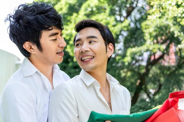 Süßer moment der liebe porträt der asiatischen homosexuellen paarumarmung und überraschungskastengeschenk zum freund konzept lgbt-homosexuelles.
