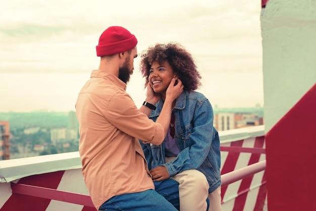 Süßer moment. hübscher junger mann, der ruhig schaut, während er seiner glücklichen lächelnden freundin gegenüber sitzt und ihr gesicht berührt