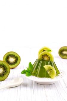 Süßer nachtischgelee-pudding mit kiwi auf weißem teller