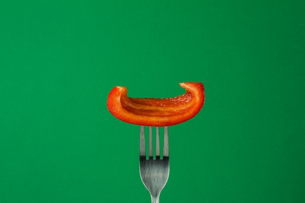 Süßer paprika auf einer gabel auf einem grünen hintergrund in einer nahaufnahme