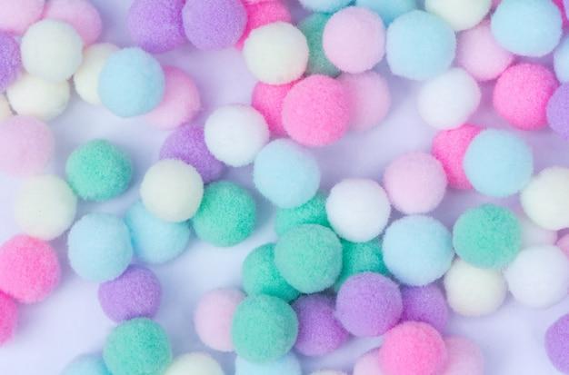 Süßer pastellfarbpom pom hintergrund