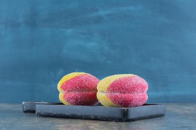 Süßer pfirsich geformte hausgemachte kekse auf dem holzbrett auf der marmoroberfläche.