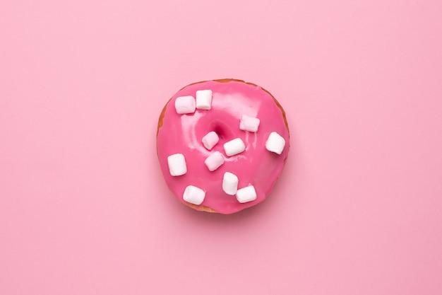 Süßer rosa donut mit eibischen auf einer rosa hintergrundebenenlage