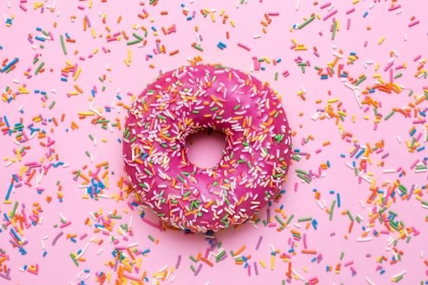 Süßer rosa donut mit mehrfarbigen streuseln auf einer rosa oberflächenebenenlage