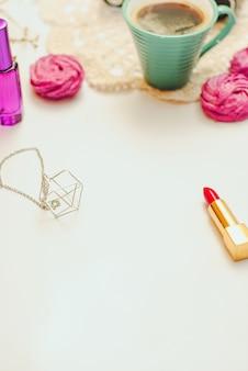 Süßer rosa eibisch - zefir, tasse kaffee und roter lippenstift auf weißem hintergrund.
