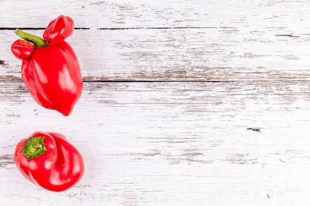 Süßer roter grüner pfeffer des lustigen hässlichen bauernhofgemüses mit veränderungen auf holztisch