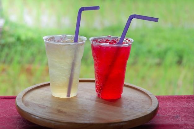 Süßer saft im plastikglas auf rundem hölzernem behälter mit dem unscharfen weiche der grünen reispaddys.