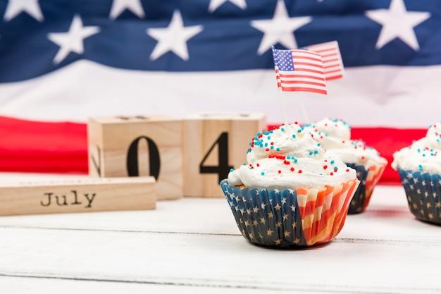 Süßer schlagsahnekleiner kuchen mit amerikanischen flaggen und hölzernen würfeln