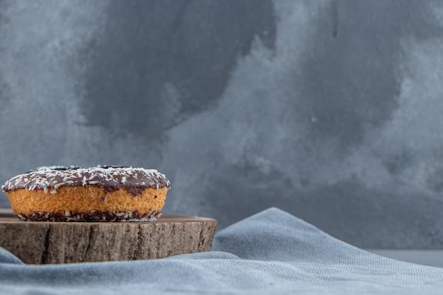 Süßer schokoladenkrapfen auf holzstück auf steinhintergrund. foto in hoher qualität