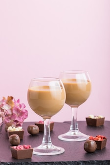 Süßer schokoladenlikör im glas mit pralinen. seitenansicht