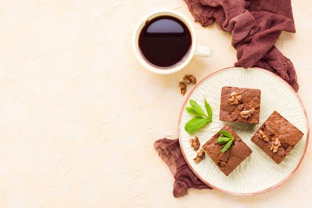 Süßer schokoladennachtisch des schokoladenkuchens mit walnüssen und gemachten blättern auf handwerksplatte und -schale