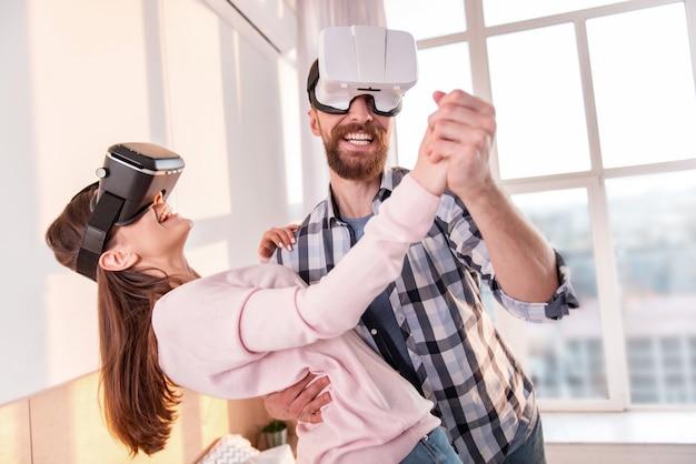 Süßer tanz. fröhliches lustiges positives paar, das vr-brille beim tanzen und lächeln trägt