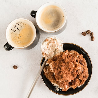 Süßer tiramisu auf weißer tabelle mit kaffee