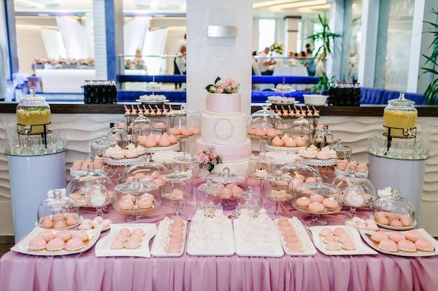 Süßer tisch. ein teller mit kuchen und muffins mit sahne. tisch mit süßigkeiten, süßigkeiten, buffet. desserttisch für eine party leckereien für die hochzeit. nahaufnahme. schokoriegel. lecker dekoriert.