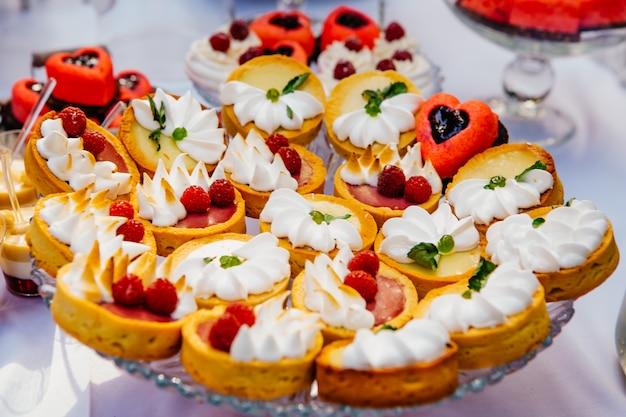 Süßer tisch mit obstkuchen mit sahne und süße. leckere schokoriegel. hochzeit schokoriegel service