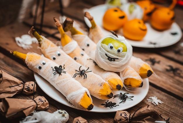 Süßer tisch mit obstleckereien für halloween.