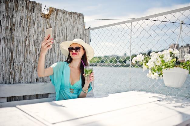 Süßer tragender hut und sonnenbrille junger dame mit einem cocktail unter verwendung ihres smartphone beim sitzen durch den see.