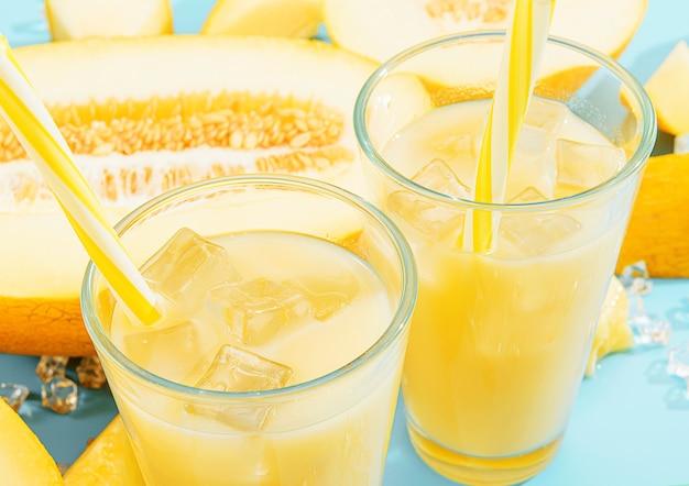 Süßer und kalter saft aus melone in gläsern vor dem hintergrund von melone in scheiben geschnitten