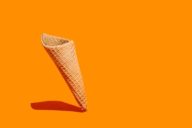 Süßer waffelkegel auf orangefarbenem hintergrund mit kopierraum