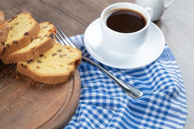 Süßer weicher kuchen serviert mit einer tasse kaffee.