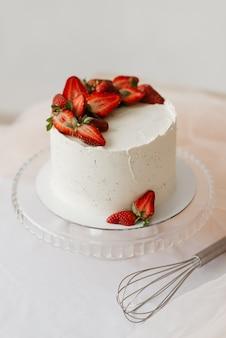 Süßer weißer kuchen mit sahne verziert mit erdbeeren auf einer tablett-draufsicht