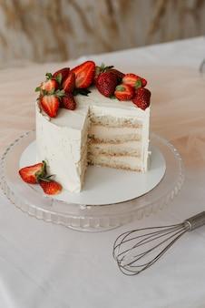 Süßer weißer sahnekuchen mit erdbeeren auf einem tablett und schneebesen