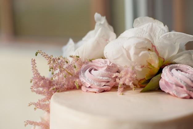 Süßer weißer sahnekuchen rund mit rosa rosenblüten und weißer pfingstrose oben drauf