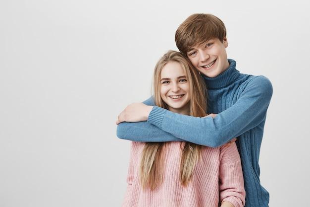 Süßer zarter innenschuss des glücklichen studentenpaares, das umarmt und kuschelt